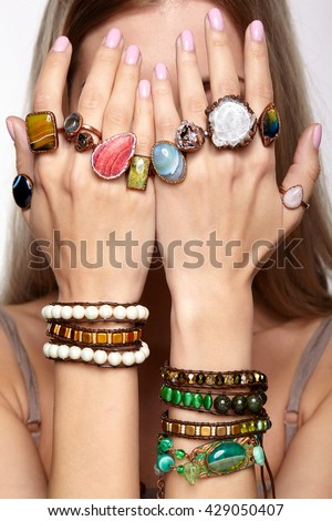 Young woman hands with multiple bracelets and fingers with many rings with stones