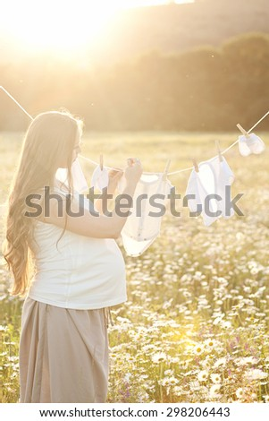 Young woman hanging up baby laundry
