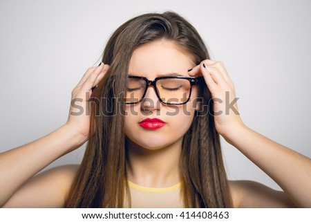 young woman has a headache, in yellow clothes close-up isolated