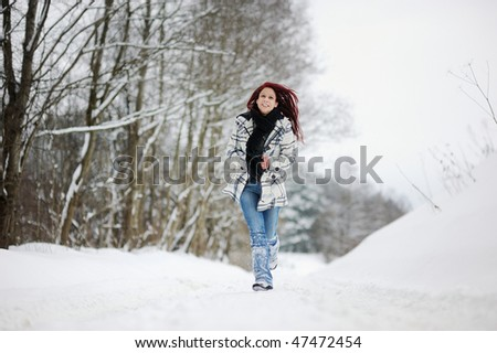 Young woman having a walk in snowy forest