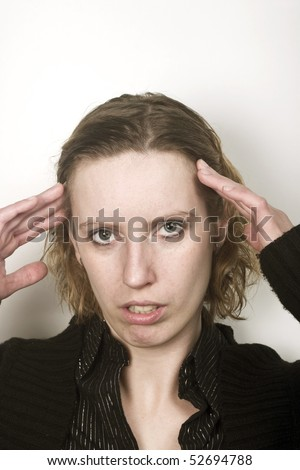 Young woman having bad migraine and feeling pain. holding her head. lots of free space above her.