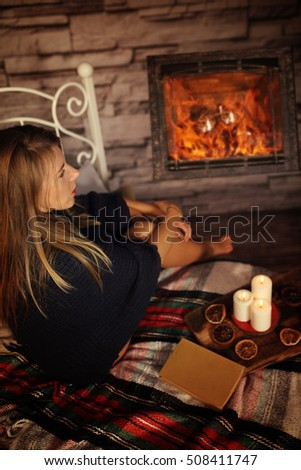 Young woman heated front of the fireplace