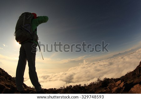 young woman hiker on sunset mountain peak