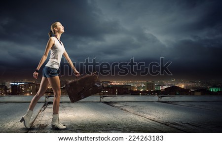 Young woman hiker walking with suitcase in hand