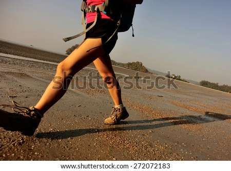 young woman hiking on sunrise beach