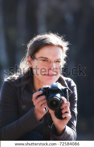 Young woman holding a camera, ready for shoot