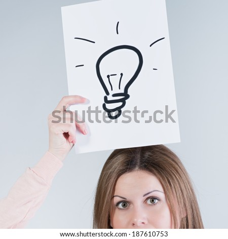 Young woman holding a paper with light bulbs. Photo in color style instagram filters