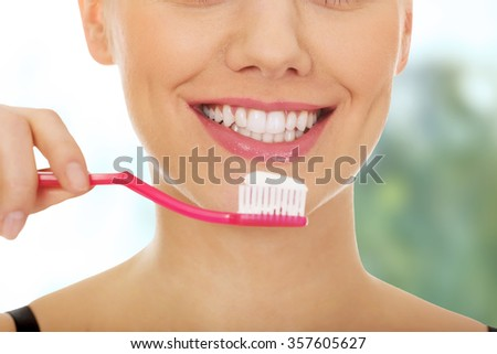 Young woman holding a toothbrush.