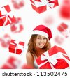 Young woman holding gift box wearing santa claus hat. Many gift boxes falling down around her - stock photo