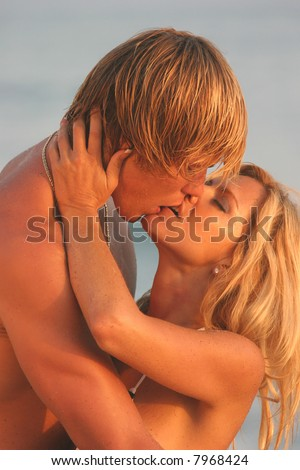 Young Woman holding her Man's face while kissing on the Beach.