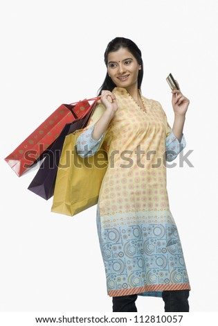 Young woman holding shopping bags and showing a credit card