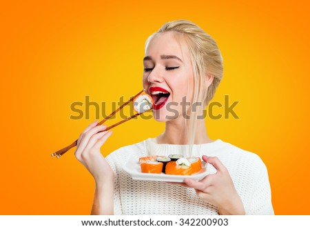 Young woman holding sushi with a chopsticks, isolated on yellow