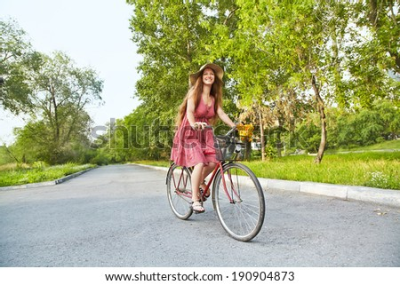 young woman in a hat riding a bicycle in a park. Active people. Outdoors