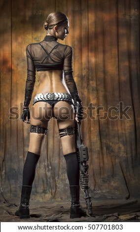 Young woman in a sexy black lingerie with a weapon. Back view