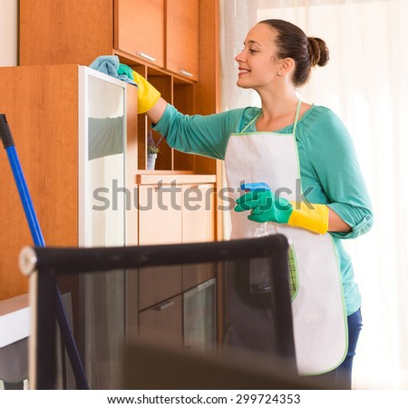 Young woman in apron making cleaning in the office-room