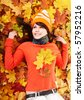 Young woman in autumn orange leaves. Outdoor. - stock photo