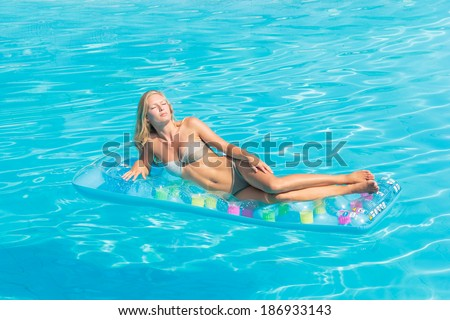 Young woman in bikini on a lilo in the swimming pool