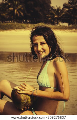 Young woman in blue swimsuit with coconut cocktail on the beach in Goa, Indi. Old lens style