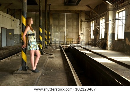 young woman in broken old factory