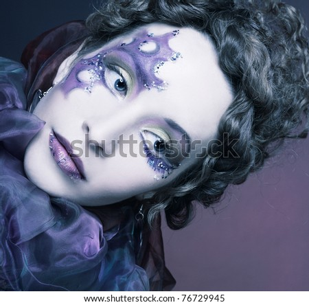 Young woman in creative image and with violet clew