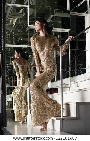 Young woman in gold dress on stairs