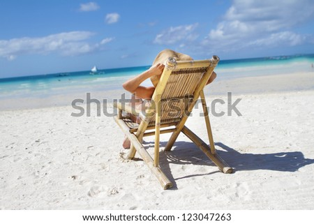 young woman in hat relaxing on beach on a deck chair