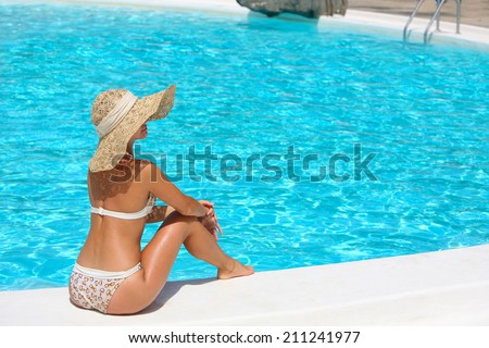 Young woman in hat sitting on the ledge of the pool.