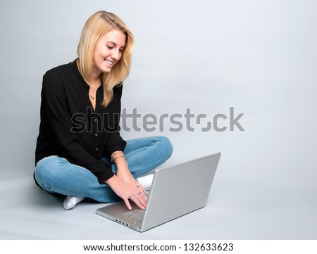 Young woman in jeans at laptop computer