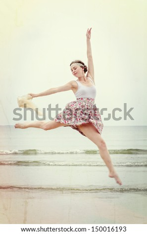 Young woman in jump with scarf on a sea shore