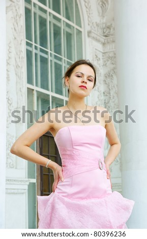 Young woman in pink dress near house