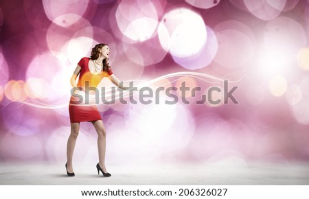 Young woman in red dress playing guitar