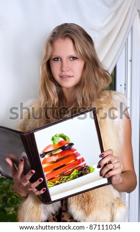 Young woman in restaurant is reading menu