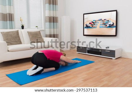 Young Woman In Sportswear Doing Yoga In Front Of Television At Home