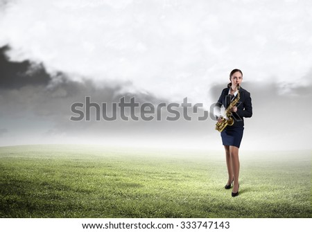 Young woman in suit with saxophone in hands