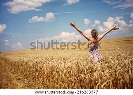 Young woman in summer dress standing in the field with raised arms