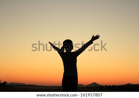 Young woman in sunset silhouette
