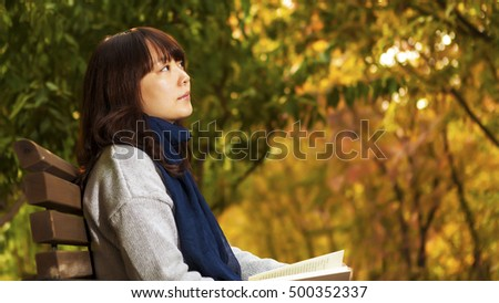 young woman in the park in the autumn, the yellow leaf background