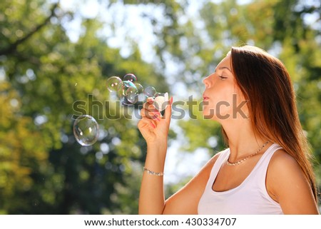 young woman inflating soap bubbles in park