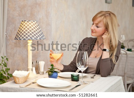 Young woman is drinking juice in restaurant