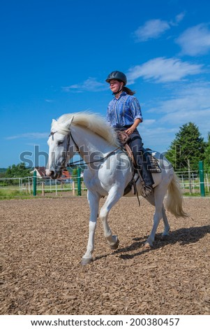 young woman is riding a white horse