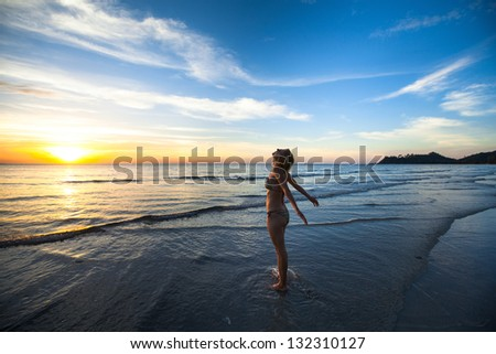 Young woman jogger at sunset on the seashore.