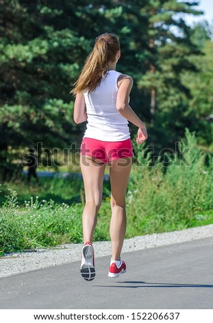 Young woman jogging in the park. Back view.