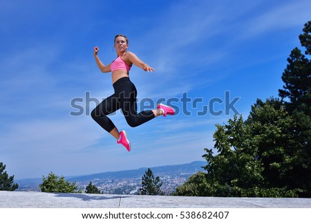 Young woman joyfully jumping in Park