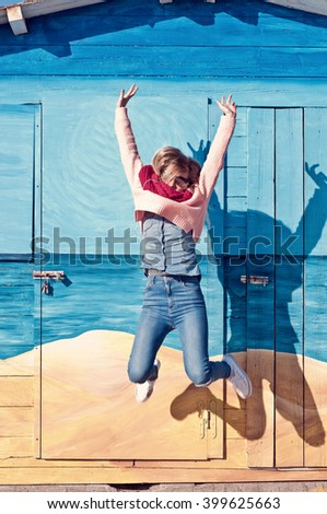 Young woman jump and listen to music with headphones.