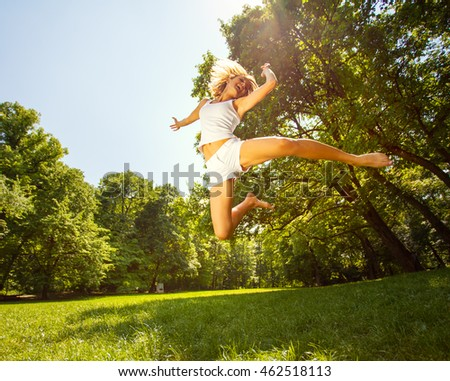 Young woman jumping at the meadow.Expressing positive energy.