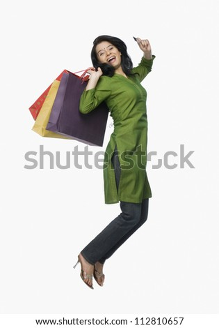 Young woman jumping with shopping bags and a credit card