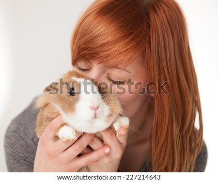 Young woman kissing her cute bunny pet.