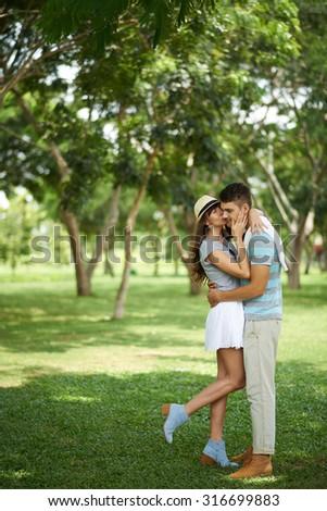 Young woman kissing her handsome boyfriend on cheek