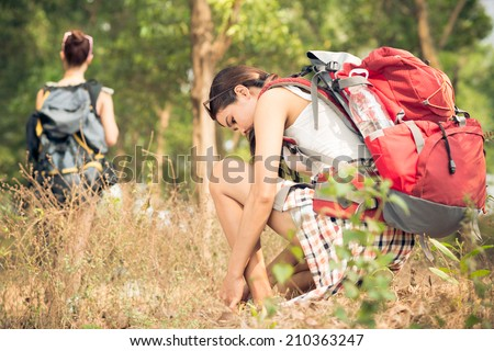 Young woman lacing up shoes before go hiking