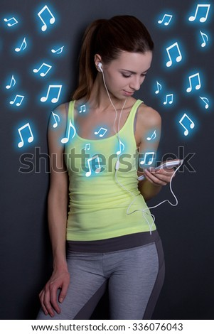 young woman listening music with phone over grey background